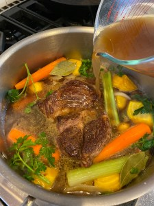 Pouring beef onto roasted beef and vegetables for mama's simple pot roast recipe-city foodie farm