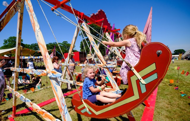 Children swinging on a wooden boat ride at 3foot People Festival in Chelmsford in 2018.