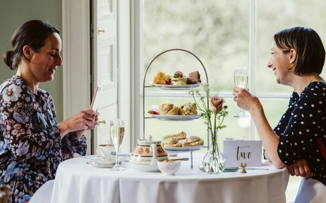 Two women take afternoon tea at Hylands House