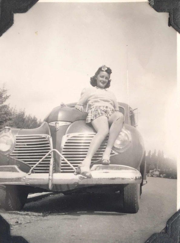 My grandmother sitting on a car hood.