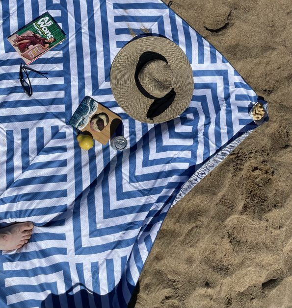 Blue and white chevron and stripe Tesalate beach towel with book, snack, and sun hate.