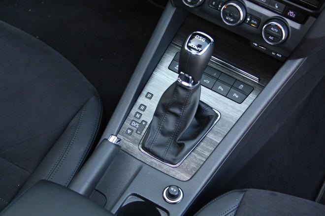Na dnu sredinske konzole se nahaja ročica odlične avtomatike, za katero se skriva tipka prilagajanja vozne dinamike. Poleg nje pa najdemo še stikali za elektrificirana prtljažna vrata in parkirne asistence. Le umetelna lesna imitacija ne prepriča.