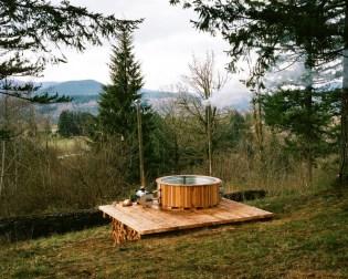 Vroča kopel na drva se nahaja tik pod drevesno hiško.