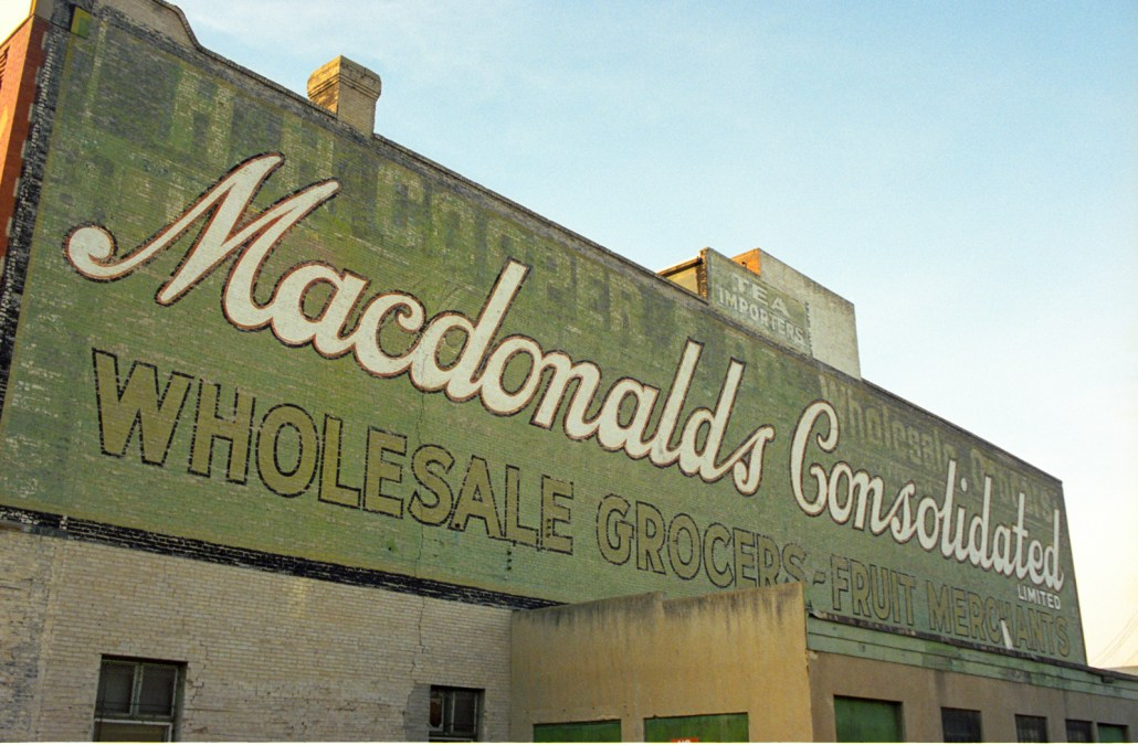 Painted sign on the side of the A Macdonald Building. Photo courtesy of Lawrence Herzog, November 1999.