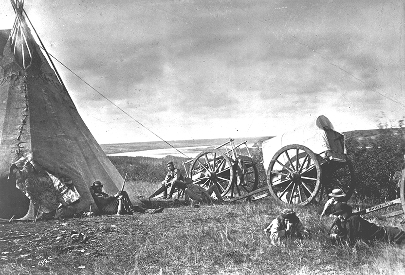A view of a teepee, two Red River carts, and men relaxing outside the tent and carts. Two of the men are holding rifles, and the North Saskatchewan river is in the background. Image created September, 1871. Image courtesy of the City of Edmonton Archives EA-10-130.
