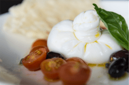 Burrata filled with crustacean oil and served with cherry tomatoes, capers and black olives. Photo by Andrew Finch