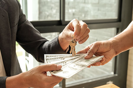 A person getting keys to their home and money back