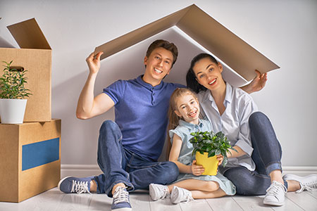 Family sitting together under a cardboard house roof