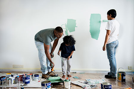 family painting house walls with green paint