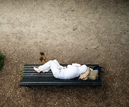 homeless person laying on bench