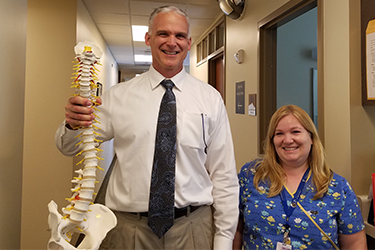 Photo of a surgeon from Puget Sound Orthopaedics holding a model skeleton by the spine next to a nurse in a doctor's office hallway smiling