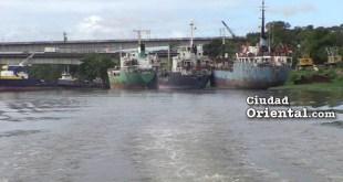 Barcos para el desguace sobre una densa capa de aceite en el río Isabela