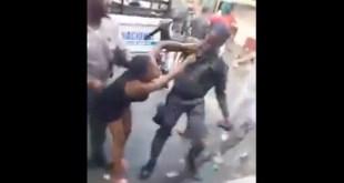 Un policía agarra a una mujer por los cabellos mientras otro la golpea con una macana