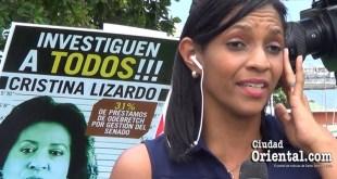 Una periodista hace un reporte en directo delante de un cartel que exige investigar a la senadora Cristina Lizardo