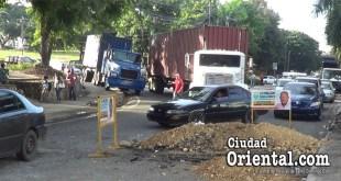 El conductor del camión azul sube su vehículo sobre la acera y obliga a los peatones a escapar.
