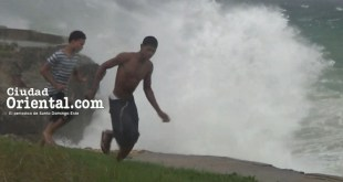 Dos hombres corren próximo a los arrecifes en la autopista Las Américas, al momento de producirse una ola rompiente al paso del huracán María