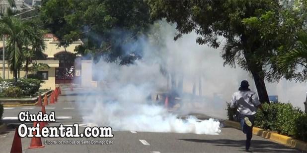 Un estudiante corre hacia una granada de gas lacrimógena para devolverla a la policía