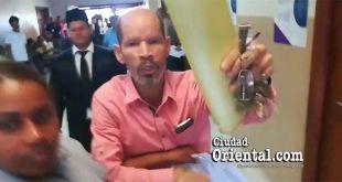 El pastor Julio Gómez es contenido por una mujer policía cuando se lanzó sobre el periodista Julio Benzant en forma agresiva.
