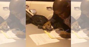 Un fiscal de SDE sostiene un fajo de billetes en una mano mientras con la otra escribe algo en un papelito