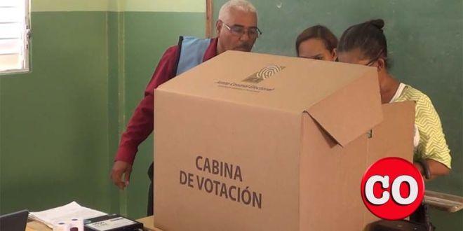 """Dos funcionarios de una mesa de votación """"ayudan"""" a un elector"""