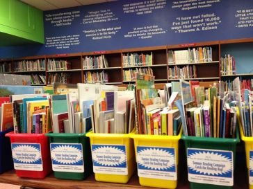 """Books in a Basket"" - the PS 22 summer reading campaign aims to get free books into the hands of neighborhood children.  Local businesses are partnering with the school by placing the baskets in their stores."