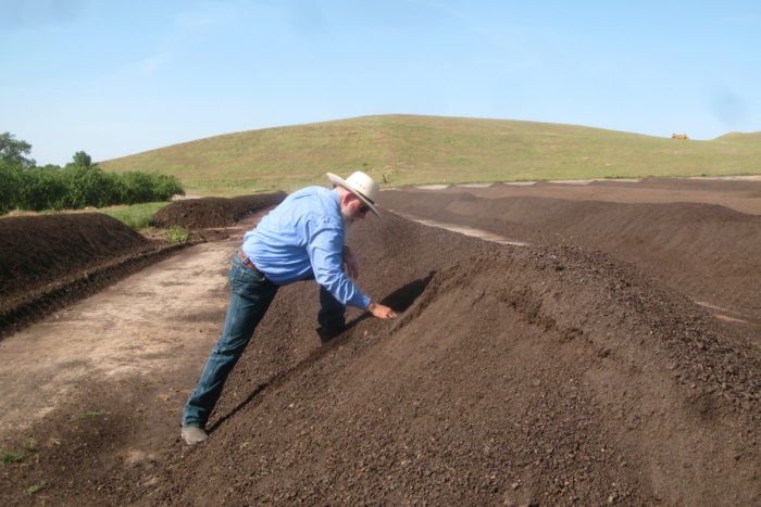 Ward Burroughs inspects compost on Burroughs Family Farms. (Photo courtesy of CalCAN)