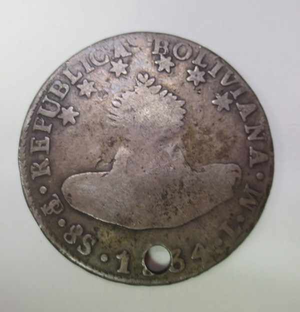 Silver coin with a hole on top