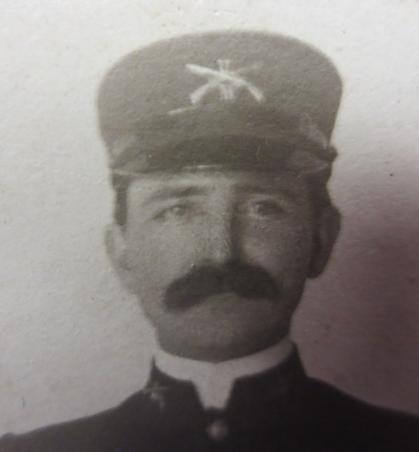 Man's face with mustache and wearing cap