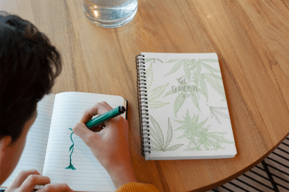 pic of person sitting at a table doodling with a Go Green Cannabis planner on the table