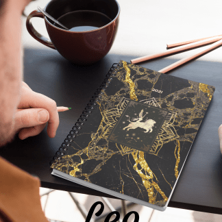 image of man sitting at black desk with a cup of coffee pencils. Black and glod Leo planner sits on desk