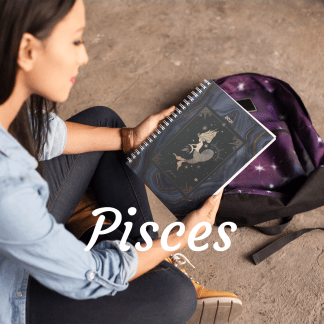 image of woman cross legged on brown floor wearing a blue shirt and black pants. holding a black grey and gold Pisces planner
