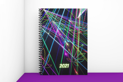 mockup of 2021 cannabis planner. cover has black background with multicolored lights criss crossing and light etched image of cannabis leaves on the cover