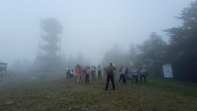 Grupa osób stojąca we mgle, w tle wieża.