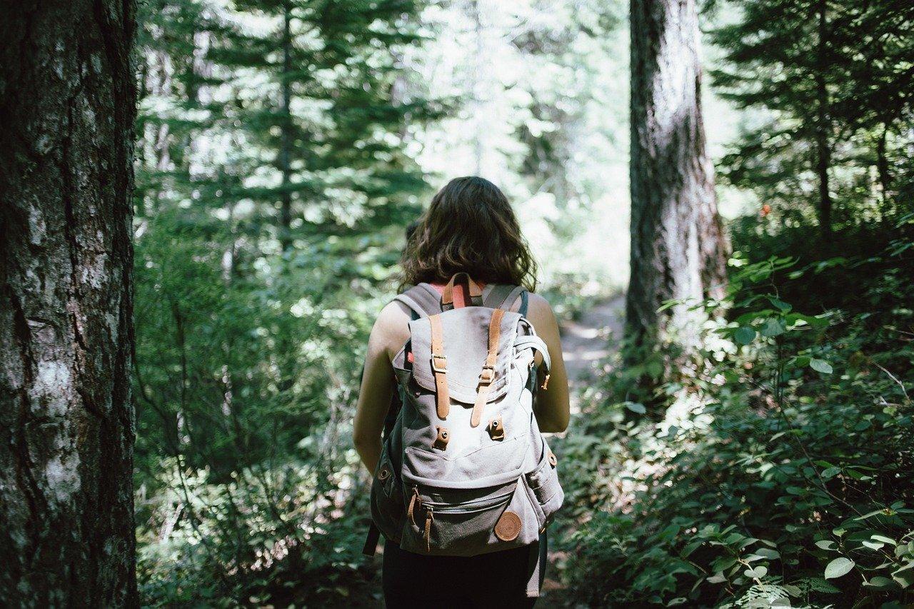 Kobieta z plecakiem na plecach w lesie