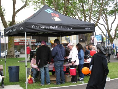 Vancouver Public Library at the National Aboriginal Day celebration, Oppenheimer Park in Vancouver's Downtown Eastside. Library staff give away books, resolve library account issues, and work with community member to design and produce buttons.