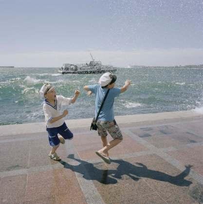 Crimea. Sevastopol. Children play in the waves on the promenade in Sevastopol. From the series 'Crimean Diaries' 2014