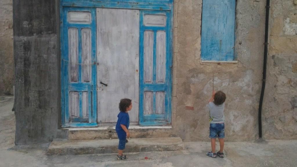 bambini che guardano una porta a marzamemi durante un weekend al mare in sicilia