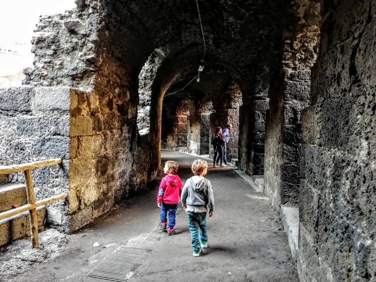 bambini che esplorano l'anfiteatro romano di Catania