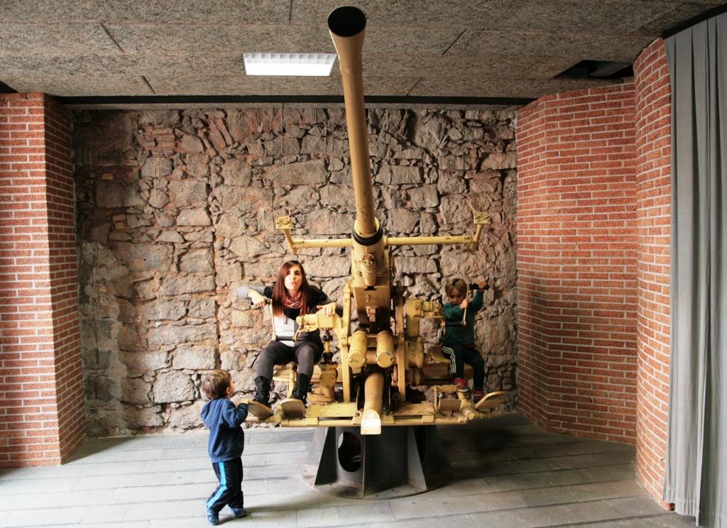 mamma e figli che giocano su un cannone contraereo al museo dello sbarco in sicilia