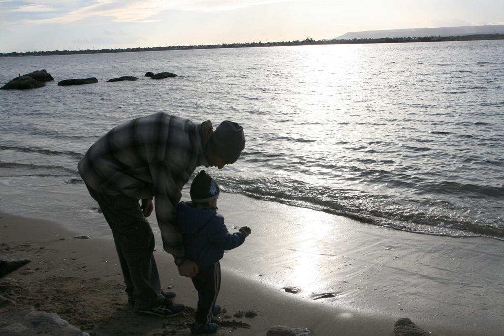 bambino che guarda il mare con il suo papà in una spiaggia a siracusa