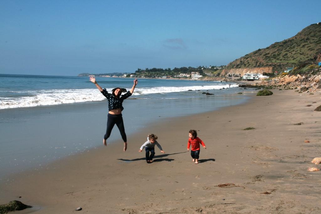 mamma e bambini che saltano nella spiaggia di Malibù in California
