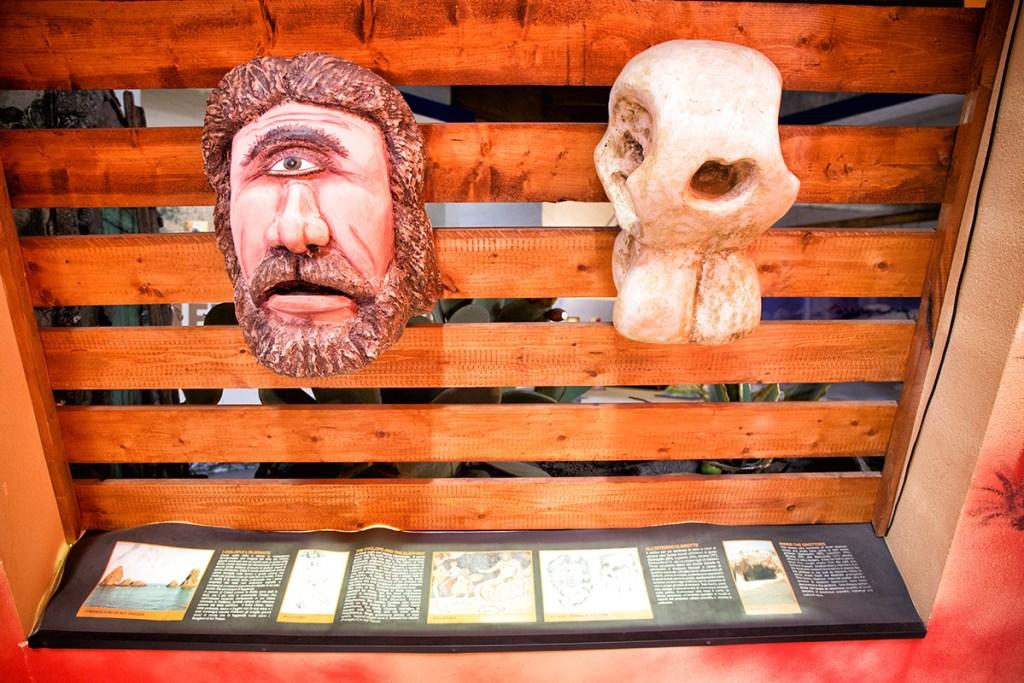 statua di polifemo accanto un cranio di elefante nano