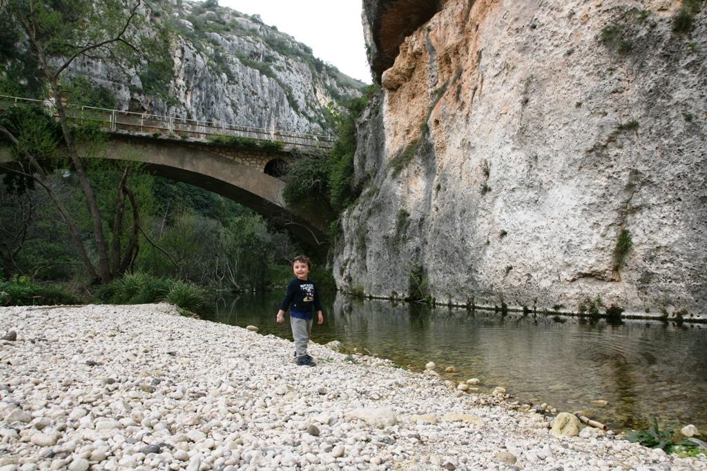 bambino che gioca sul greto del fiume