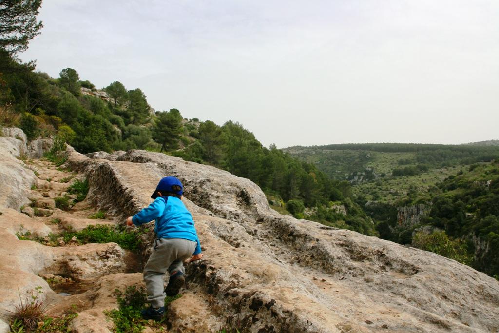 un bambino che gioca a Pantalica in Sicilia