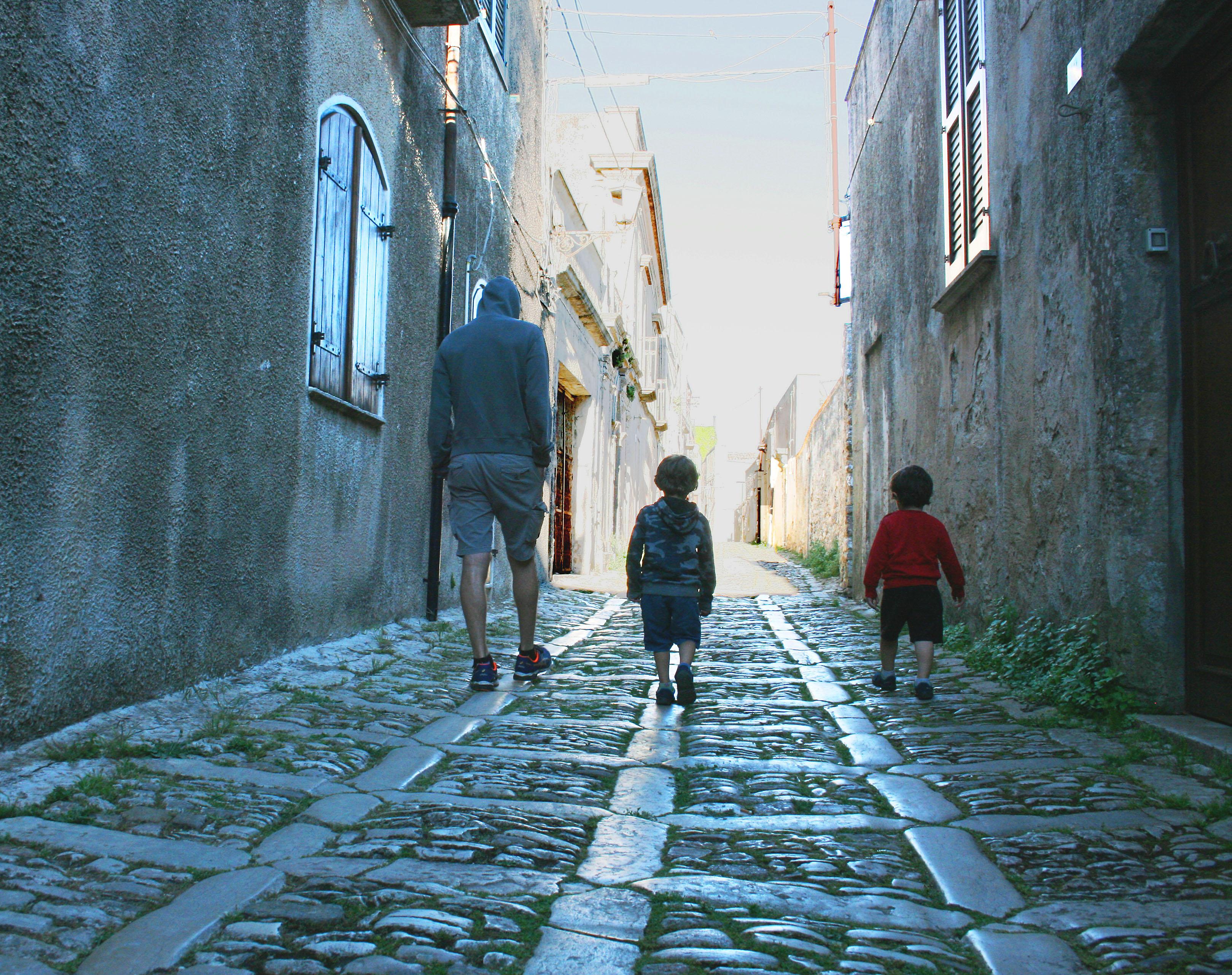 papà e bambini che camminano a Erice