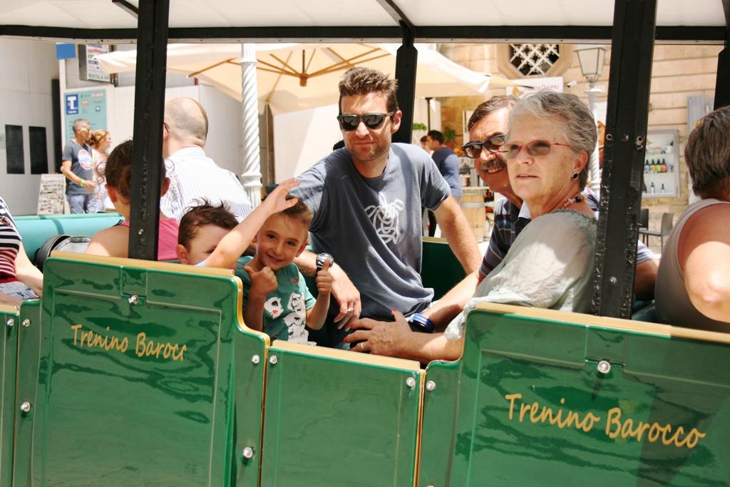 una famiglia con bambini a bordo del trenino barocco di Ragusa Ibla