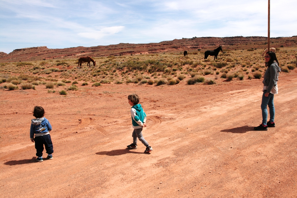 bambini che guardano i cavalli vicino monument valley