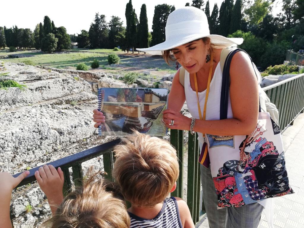 una guida che spiega ai bambini al Parco-Archeologico-della-Neapolis-di-Siracusa