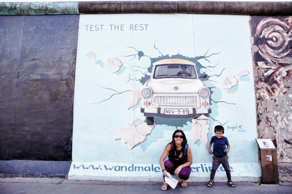 mamma e bambino davanti un murales di berlino