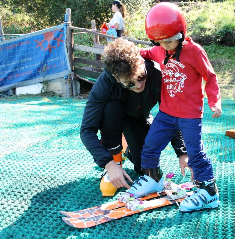 un bambino che fa una lezione di sci